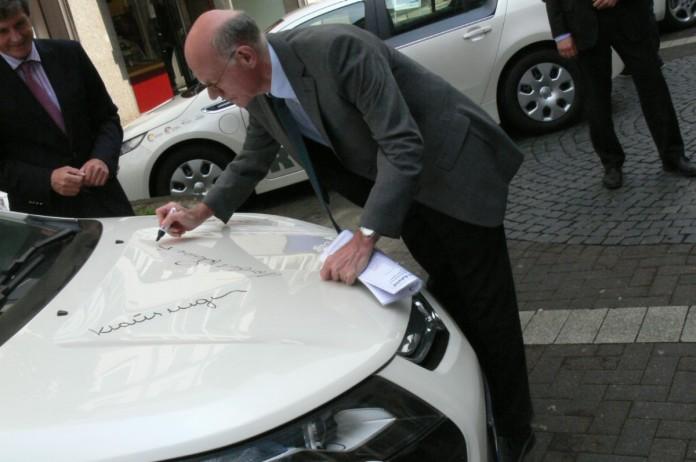 Norbert Lammert unterzeichnet einen Opel Ampera