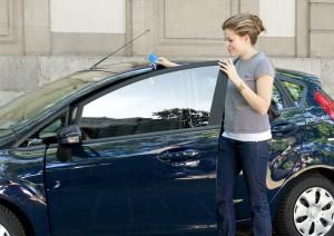Frau an einem Stadtmobil Fahrzeug