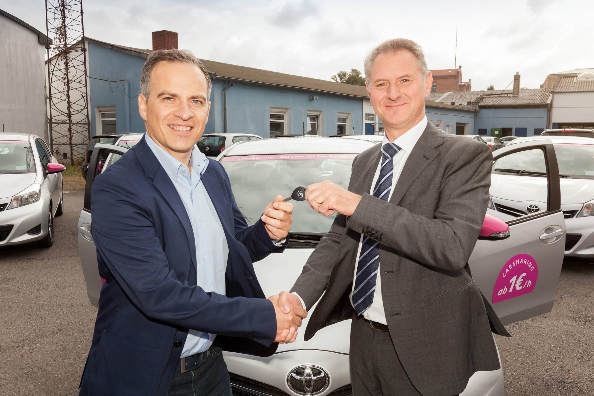 Mauro Mariani (COO CiteeCar) und Michael Heise (Geschäftskundenservice Toyota) bei der Schlüsselübergabe.