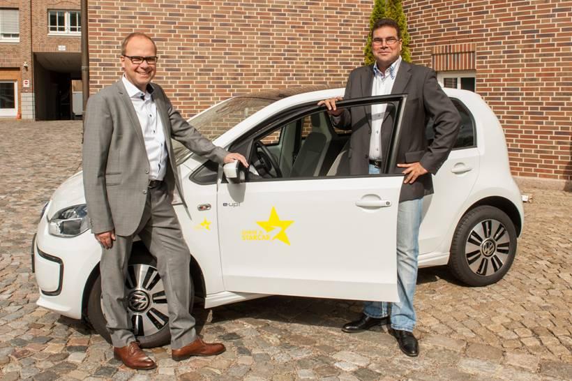 """Martina van Kann - Die Starcar-Geschäftsführer Olaf Puttlitz (links) und Maik Grabow präsentieren den elektrobetriebenen Volkswagen """"e-Up""""."""