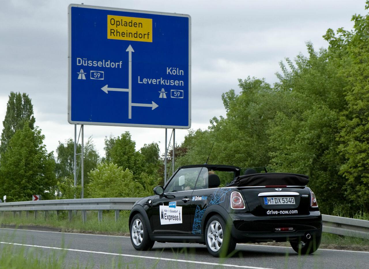 DriveNow Mini an einem Schild nach Köln und Düsseldorf